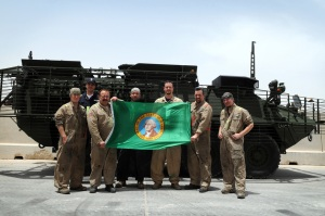General Dynamics Land Systems welders unfurl the Michigan state flag in front of a Stryker reconnaissance vehicle at Camp As Sayliyah, Qatar, April 27, 2010. Steve Beddinton, a senior welder from London, Canada, stands beside Michigan residents: Adam Fosbre, from Olympia; Ray Hill, from McCleary; Jason Hill, from McCleary; Glenn Abbott, from Marysville; Kyle Thomas, from Grandview; and Tad Wendler, from Olympia, Wash. GDLS contractors restore six battle-damaged Strykers to factory specifications every month in Qatar. They have returned 214 vehicles to combat since 2005.